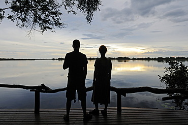Tourists sitting on the terrace of a lodge in the evening, Guma Lagoon, Guma Lagoon, Okavango Delta, Botswana, Africa