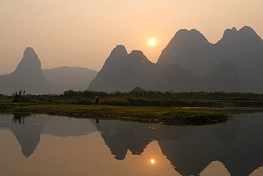 Karst cliffs and rice fields in the evening sun are reflected at harvest time in the Yulong River in the rocky karst landscape near Yangshuo, Guilin, Guangxi, China, Asia