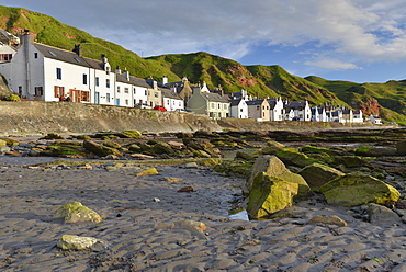 Algae-covered rocks at low tide and houses in the Seatown area of Gardenstown, Banffshire, Scotland, United Kingdom, Europe