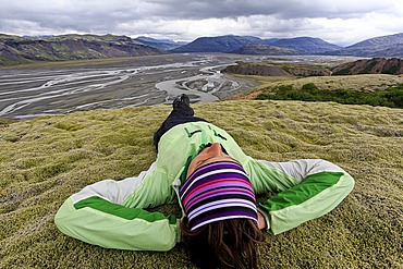 Young woman lying in a moss landscape, Sandur of Vatnajoekull, Iceland, Europe
