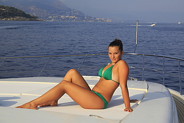 Young woman wearing a green bikini sitting on the front sun deck of a motor yacht, French Riviera, Cote d'Azur, Mediterranean Sea, Europe