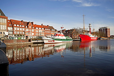 Museum ships are reflected in the water of the Ratsdelft in the harbour of Emden, East Frisia, Lower Saxony, Germany