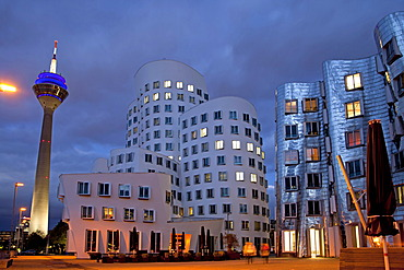 A building by American architect Frank O. Gehry and the Rheinturm tower at night, Neuer Zollhof building complex, Medienhafen district, Duesseldorf, North Rhine-Westphalia, Germany, Europe