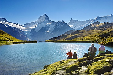 Walkers having a rest next to Bachalpsee lake near Grindelwald First, Swiss Alps, Canton of Bern, Switzerland