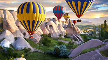 Hot air balloons over Goreme volcanic tuff rock formations at dawn, Cappadocia, Turkey