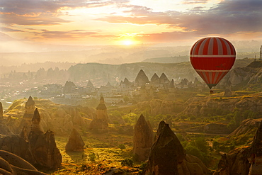 Hot air balloon over volcanic tuff rock formations at dawn, Goreme, Cappadocia, Turkey