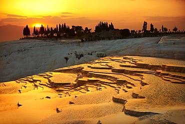 Pamukkale travetine terrace, white calcium carbonate rock formations, at sunset, Turkey
