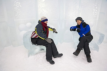 Two women sitting on chairs carved out of ice in the Icehotel in Jukkasjaervi, Lappland, North Sweden, Sweden