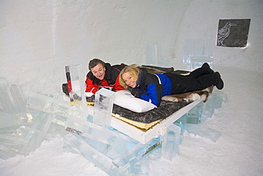 Man and woman lying on a bed in a bedroom of the Icehotel in Jukkasjaervi, Lappland, North Sweden, Sweden