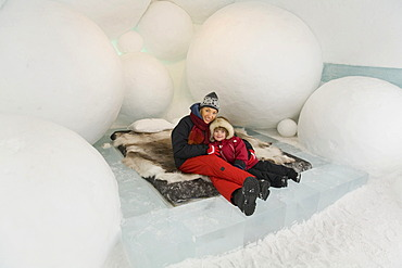 Woman and a 4-year-old girl sitting on a bed in a hotel room of the ice hotel in Jukkasjaervi, Lappland, Northern Sweden