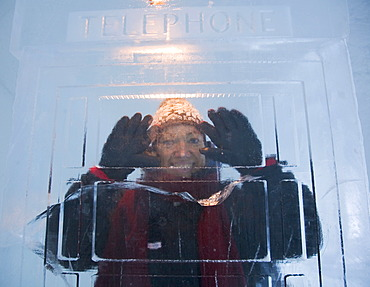 Woman in a telephone booth made of ice, ice hotel of Jukkasjaervi, Lappland, Northern Sweden