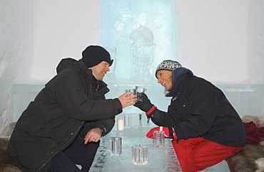 Ice bar of the ice hotel of Jukkasjaervi, woman and man clinking ice glasses, Jukkasjaervi, Lappland, Northern Sweden