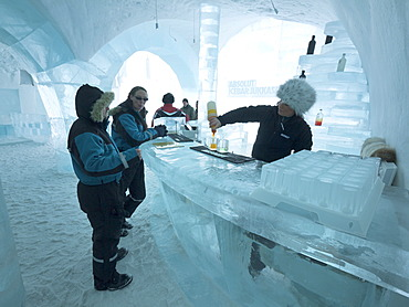 Visitors standing in the Absolut ice bar in the ice hotel in Jukkasjaervi, Kiruna, Lappland, northern Sweden, Sweden, Europe