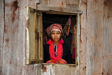 Young woman of the Akha Pala tribe looking out of a window dressed in a colourful head-dress and a red necklace, Ban Saenkham Tai, Phongsali Province, Laos, South East Asia