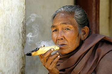 Portrait of a smoker, old woman smoking a hand-rolled cigar, Bagan, Burma, South East-Asia