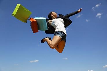 Woman jumping with shopping bags, joyful leap