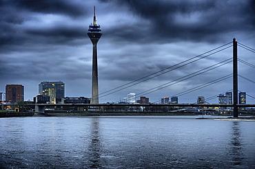 Rheinturm tower with the Rhine and the skyline at dusk, Medienhafen, Media Harbour, Duesseldorf, North Rhine-Westphalia, Germany, Europe