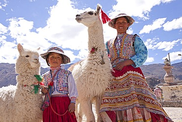 Woman and girl with llama and alpaca in Maca near Colca Canyon, Peru, South America