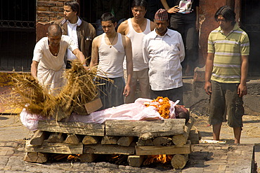 Traditional funeral, people standing around a body on a pyre, while an untouchable priest of the lowest caste spreads wet reed over the body, Pashupatinath, Nepal, Asia