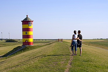 Couple strolling in front of Pilsum Lighthouse, Pilsum, Krummhoern, East Frisia, Lower Saxony, Germany, Europe