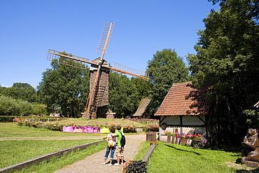 Visitors in front of the Bockwindmuehle windmill at the Muehlenhof Open-Air Museum, Muenster, North Rhine-Westphalia, Germany, Europe