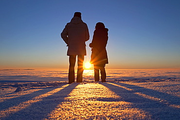 Two people standing in front of sunset on Schauinsland Mountain in the Black Forest, Baden-Wuerttemberg, Germany, Europe