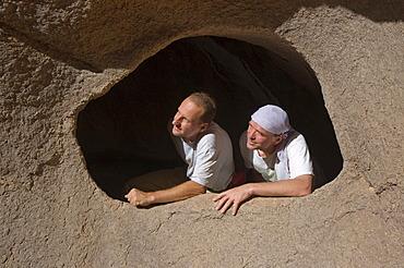 Man looking through a hole in the rock, Jebel Uweinat, Jabal al Awaynat, Libya