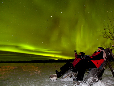 Young couple, woman and men, sitting in a wooden chair, watching northern polar lights, pointing, Aurora Borealis, green, near Whitehorse, Yukon Territory, Canada
