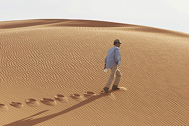 Man is walking along a sanddune, Lybia