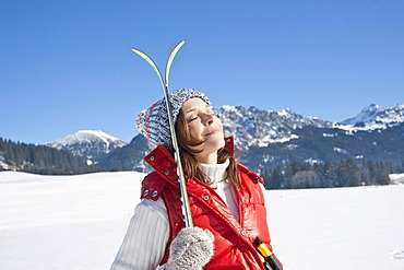 Woman with cross-country skis in the mountains