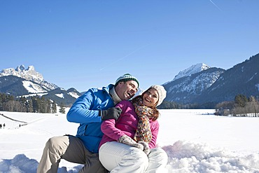 Couple sitting on a sledge in the mountains