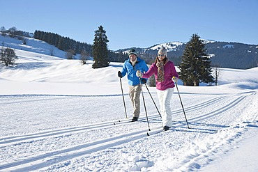 Couple cross-country skiing in the mountains