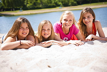 Group of girls sitting on the beach of a lake