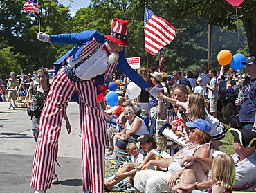 Uncle Sam on stilts greets the crowd at the July 4 parade in a small New England town, Amherst, New Hampshire, USA