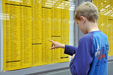 School boy, 9, studying the train timetable, Central railway station in Cologne, North Rhine-Westphalia, Germany, Europe