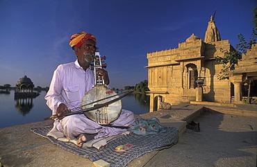 Busking at Gadi Sagar with Hindu temple, Jaisalmer, Rajasthan, India, Asia