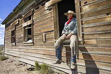 Cowboy sitting in barn window, wildwest, Oregon, USA