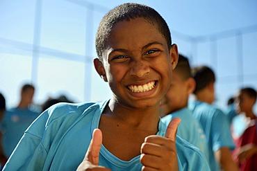 Boy making thumbs-up gesture, Guararape favela, Rio de Janeiro, Brazil, South America