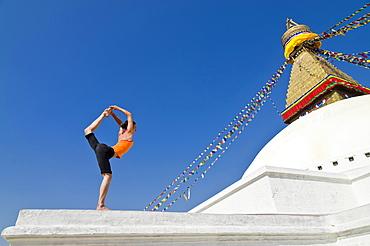 Young woman practicing yoga at Boudnanath stupa, showing the Natarajasana pose, or Lord Shiva's pose, Kathmandu Valley, Kathmandu, Kathmandu District, Bagmati Zone, Nepal, Asia
