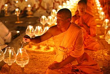 Monk lights candle, meditation, Wat Phra Dhammakaya Temple, Khlong Luang District, Pathum Thani, Bangkok, Thailand, Asia