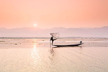 Inle lake fisherman standing on a longtail boat in the distinctive leg rowing stance used by the Intha people, Inle lake, Myanmar, Asia