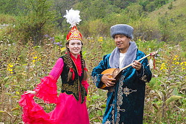 Kazakh man singing and playing the dombra for a woman, Kazakh ethnographic village aul Gunny, Talgar, Almaty, Kazakhstan, Asia
