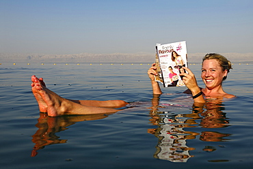 Young woman reads newspaper floating in Dead Sea, Jordan, Asia