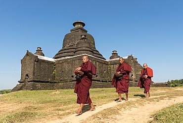 Buddhist monks collect morning alms in front of Laymyetnha Paya, Lemyethna Temple, Mrauk U, Burma, Myanmar, Asia