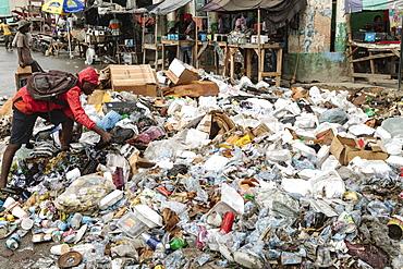 Man rummages in garbage, garbage dump, roadside, Port-au-Prince, Ouest, Haiti, Central America