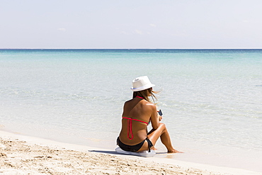 Woman sitting down by the sandy beach, Puglia, Italy, Europe