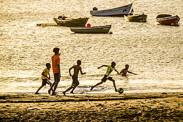 Teenager playing soccer, children, evening mood, city beach of Tarrafal, São Nicolau, Cape Verde, Africa