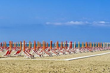 Empty orange deckchairs and sunshades on beach, early season, Viareggio, Tuscany, Italy, Europe