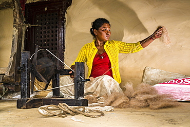 Native woman spinning sheep's wool with traditional spinning wheel in front of house, Ghandruk, Kaski District, Nepal, Asia