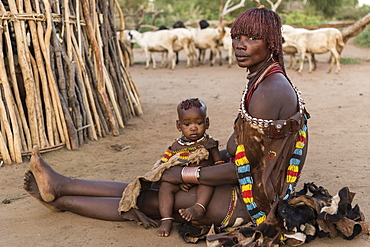 Woman with toddler sitting in front of mud hut on the ground, Hamer tribe, Turmi, region of southern nations, Ethiopia, Africa
